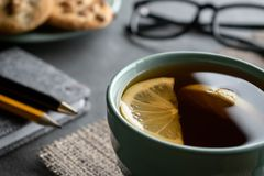 Black tea with lemon slices on a napkin of burlap with notepad pen, a pencil a plate of cookies and glasses stock image