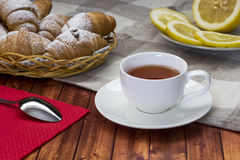 Black tea with lemon. On a table next to the croissants Royalty Free Stock Photo
