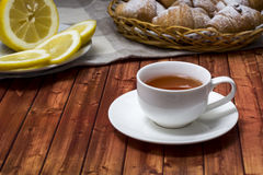 Black tea with lemon. On a table next to the croissants Royalty Free Stock Images