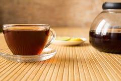 Black tea and a lemon on the table. Black tea and a lemon on the wooden table royalty free stock photography