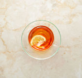 Black tea with lemon in the transparent mug on a marble backgrou Stock Photography