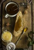Black tea in an metal mug and bread with honey on wooden Board. The Black tea in metal mug and bread with honey on wooden Board, Flatley Stock Photography