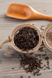 Black tea in metal strainer on a wooden table Royalty Free Stock Photo