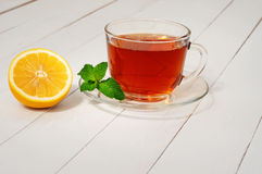 Black tea with mint and lemon in a cup Royalty Free Stock Images