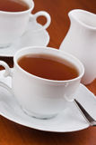 Black tea in mugs with saucers Stock Images
