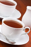 Black tea in mugs with saucers Stock Photo