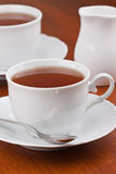 Black tea in mugs with saucers Stock Photos
