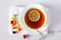 Black tea and multicolored drops Stock Photography