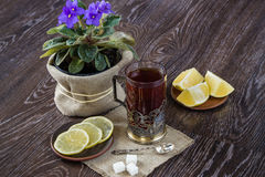 Black tea in old-fashioned glass with lemon on dark background Stock Photo