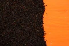 Black tea on an orange background Royalty Free Stock Photo