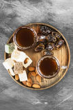 Black tea, oriental sweets, dates and nuts on a dark background. Stock Photography