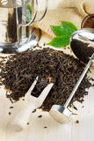 Black tea pile, teapot, wooden scoop Royalty Free Stock Images