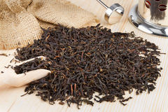 Black tea pile, wooden scoop, teapot Royalty Free Stock Photo