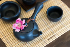 Black tea pot and cup. On bamboo mat Royalty Free Stock Photo