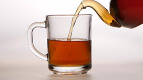 Black tea is poured from teapot into a glass cup. Black tea is poured from teapot into glass cup, transparent glass kitchen utensils, man hand holds teapot with stock video
