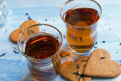 Black tea served in two Turkish cups. Closeup of black tea served in two Turkish cups with heart shaped gingerbread cookies royalty free stock image