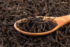 Black tea in a spoon. On a black tea background. Close-up shot royalty free stock photos
