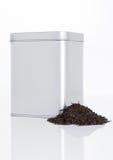 Black tea steel jar with loose tea next to it Royalty Free Stock Image