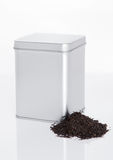 Black tea steel jar with loose tea next to it Royalty Free Stock Images