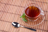 Black tea on table. Black tea in glass cup with pepper mint and spoon Stock Image