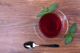 Black tea on table. Black tea in glass cup with pepper mint and spoon Stock Photos
