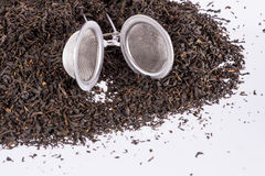 Black tea and tea strainer on white background. Stock Photos