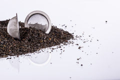 Black tea and tea strainer on white background. Stock Image