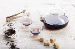 Black tea in a transparent teapot and cups Royalty Free Stock Photos