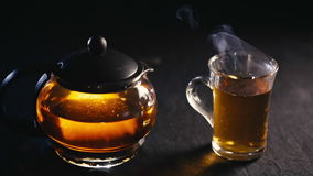 Black tea in a transparent teapot tea in glass Cup on black background stock video