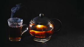 Black tea in a transparent teapot tea in glass Cup on black background.  stock footage