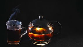 Black tea in a transparent teapot tea in glass Cup on black background.  stock video