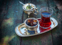 Black tea Turkish glass with slices of sugar on a silver platter. Vintage toning Stock Images