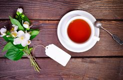 Black tea in a white round cup with a saucer. And an iron spoon on a brown wooden table, next to a bouquet of flowering jasmine with a paper tag, top view Stock Images