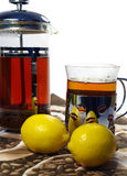 Black tea whith lemon in the mug and kettle Royalty Free Stock Photos