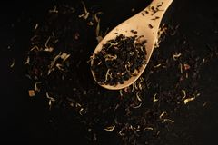 Black tea in a wooden spoon on a black tea background. Close-up stock photo