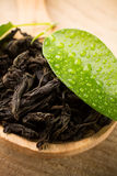 Black tea. Black tea wooden spoon with a green leaf, wood surface Stock Photography