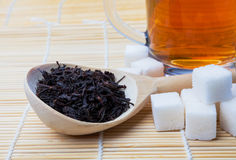 Black tea in a wooden spoon, sugar cubes and a mug of tea on the. Black tea in a wooden spoon, sugar cubes and a mug of black tea on the mat Royalty Free Stock Photo