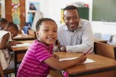Black teacher and elementary school girl smiling to camera Stock Photos