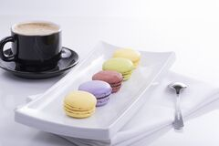 Black Teacup and 5 French Macaroons on Plate Royalty Free Stock Photo