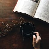 Black Teacup Filled With Coffee Beside Flower and Book Stock Images