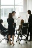 Black team leader teaching diverse business people at group meet. Black female team leader teaching diverse business people at meeting, multiracial executive stock photos