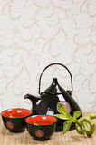 Black teapot. With  2 cups  and a lucky bamboo Stock Images