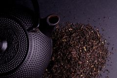 Black Teapot with Healthy Tea Leaves Stock Photography