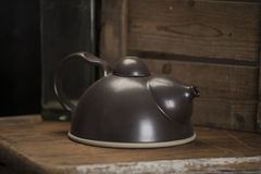 Black Teapot with Lid on Wooden Counter. Black teapot with cover on a wooden counter Stock Photos