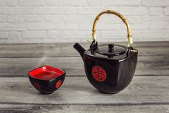 Black teapot and square cup full of hot tea with steam, with red stock photo