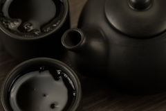 Black teapot, two cups on old wooden background. Royalty Free Stock Image