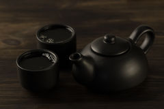 Black teapot, two cups on old wooden background Royalty Free Stock Images
