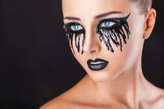 Black tears. Closeup of a beautiful woman with fantasy makeup with black tears and lips on a black background Stock Image