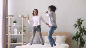 Mixed race mother and daughter enjoy music dancing on bed. Black teen daughter wearing headphones have fun with mother use earphones enjoy listen favourite music stock video