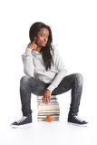 Black teenage student girl sits on education books Stock Photos